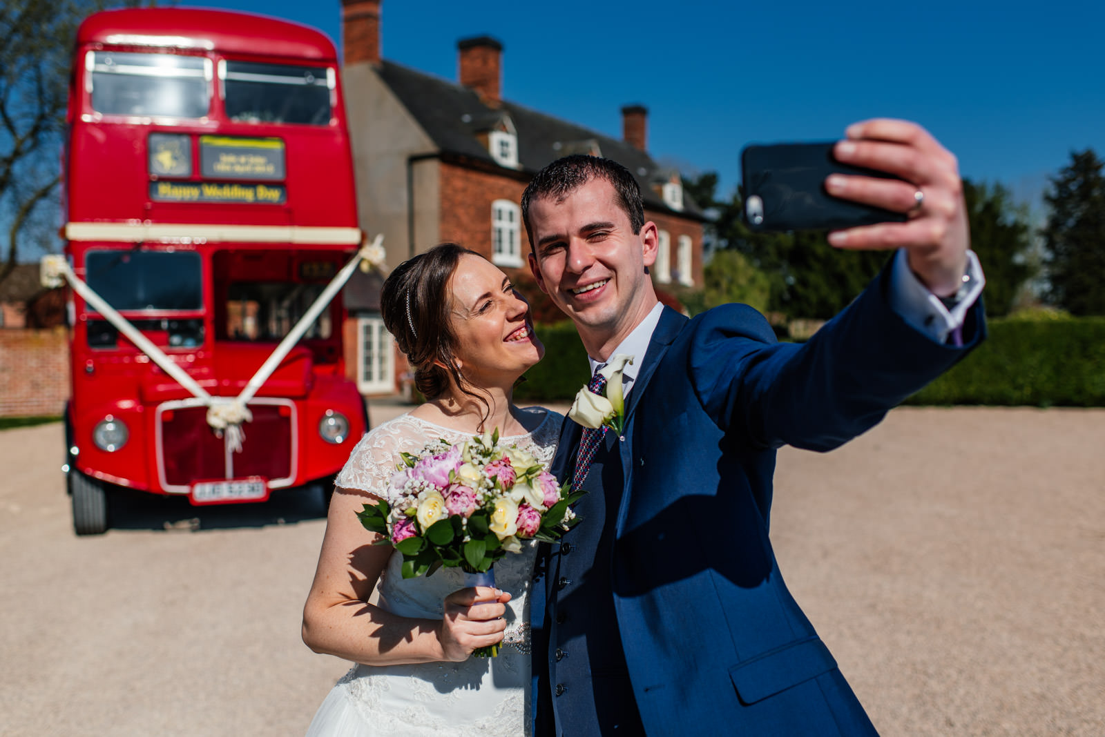 Bride and groom selfie routemaster wedding bus