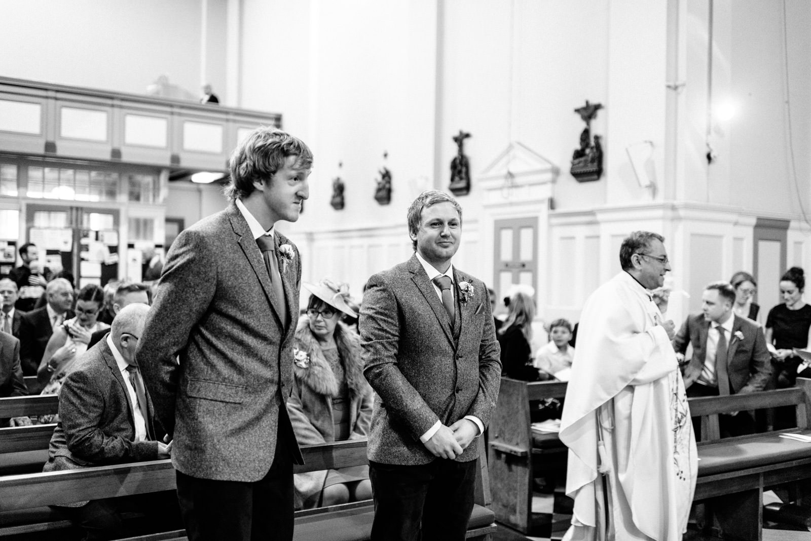 Best man and groom waiting for bride in church