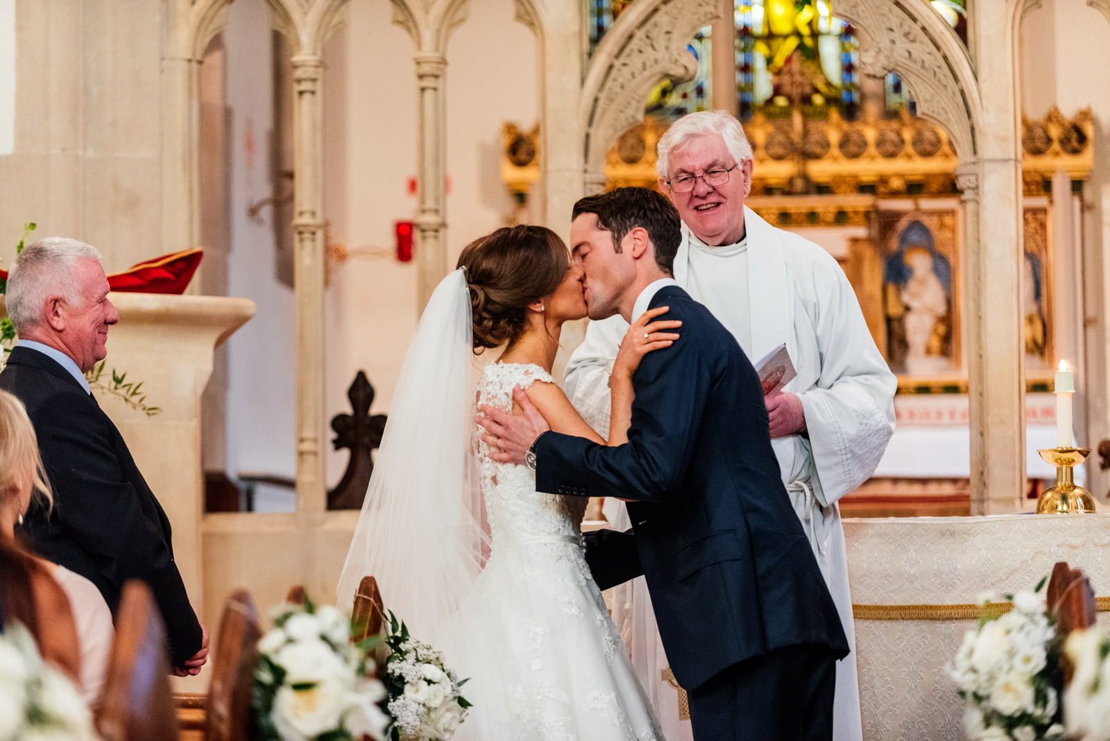 First kiss of bride and groom at church wedding