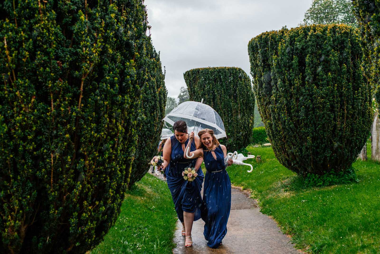 Bridesmaids arriving in at church in the rain