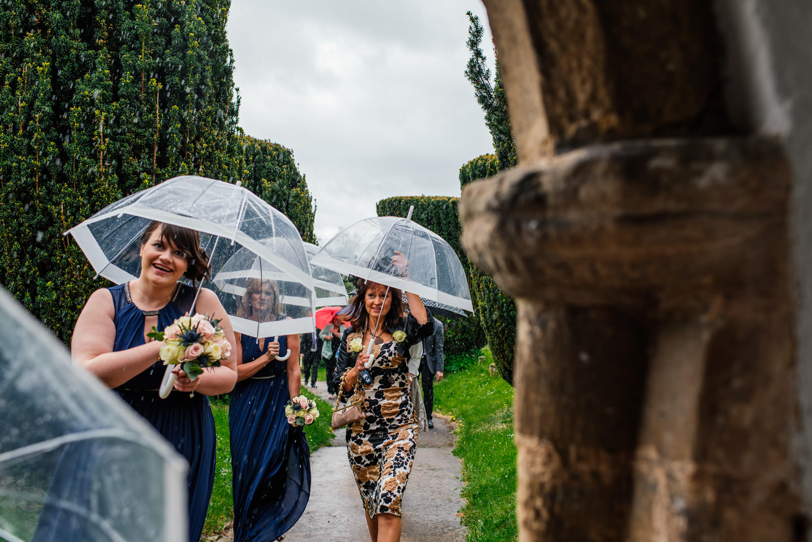 Guests arriving at wedding in the rain