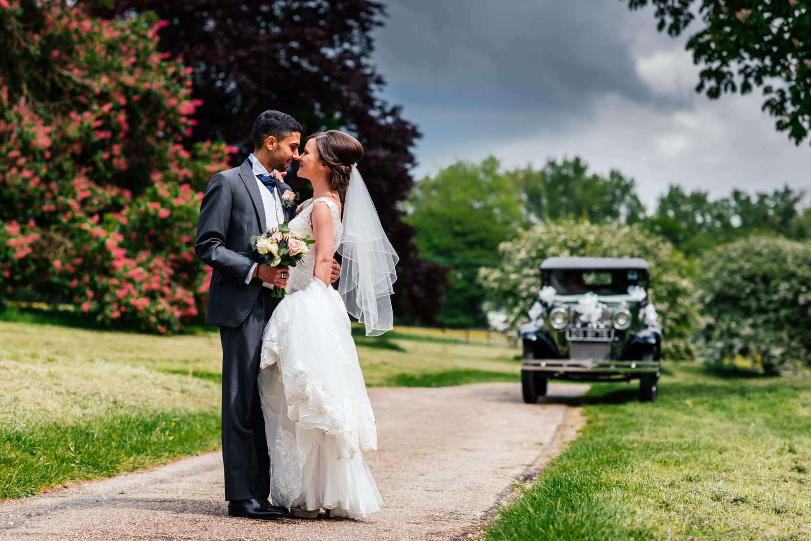 Bride and groom portrait with vintage car