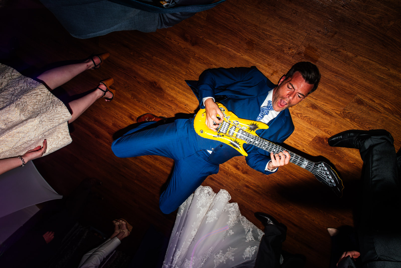 Guest on dance floor with inflatable guitar