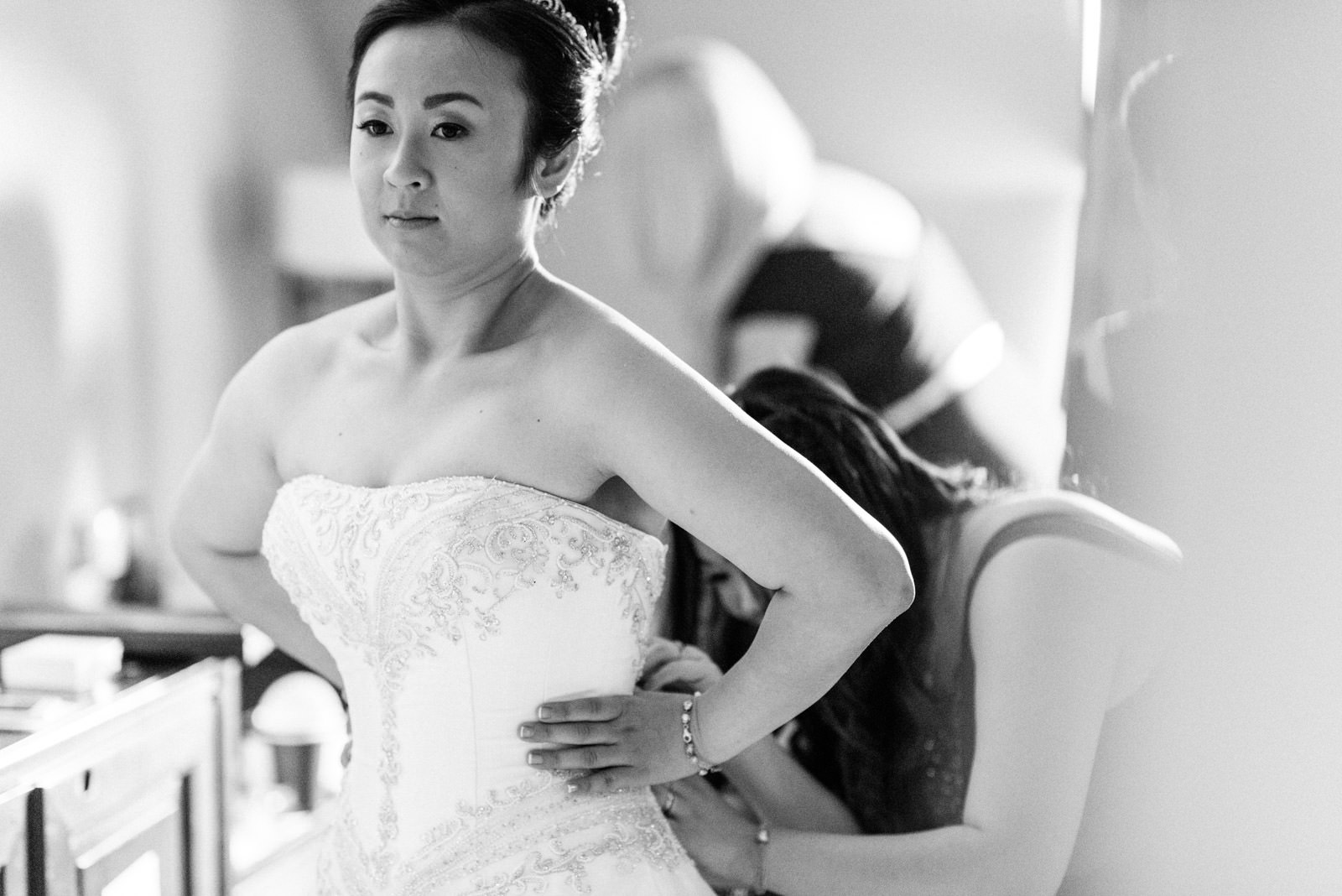 black and white photo of bride getting wedding dress fitted