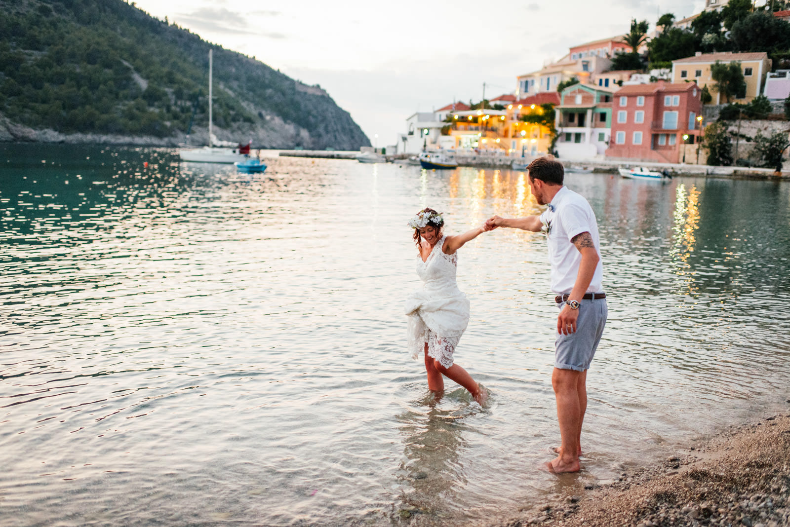 bride and groom paddle in the sea at assos wedding