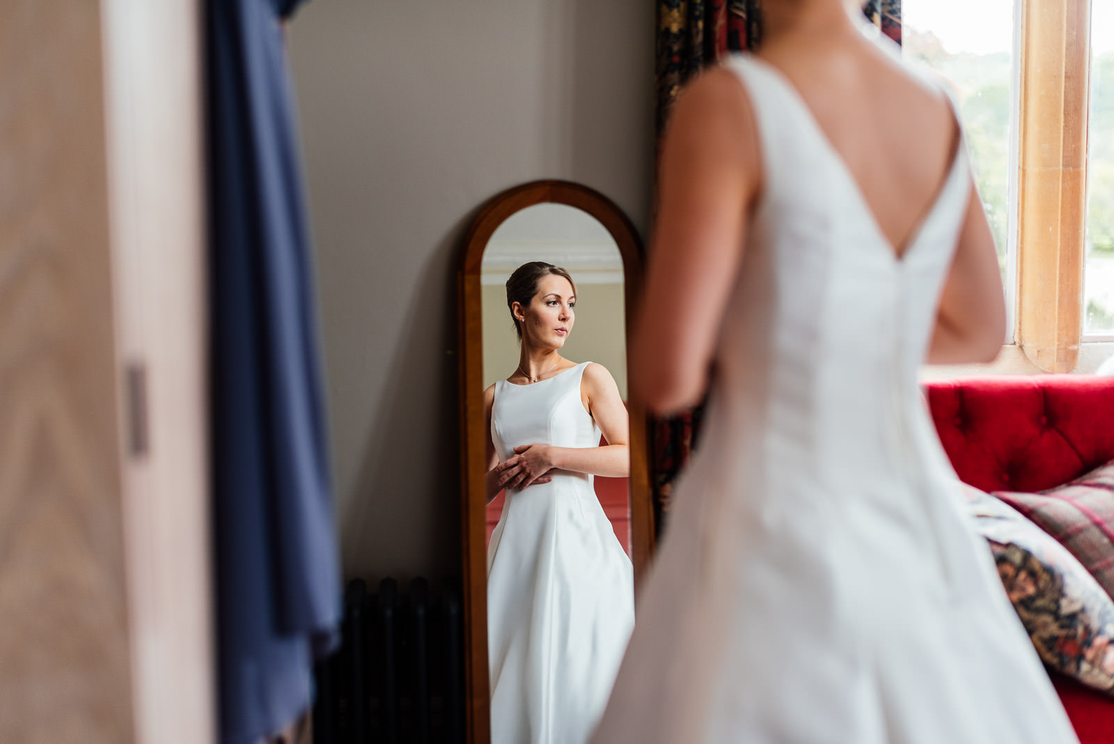 bride looking in mirror at dress