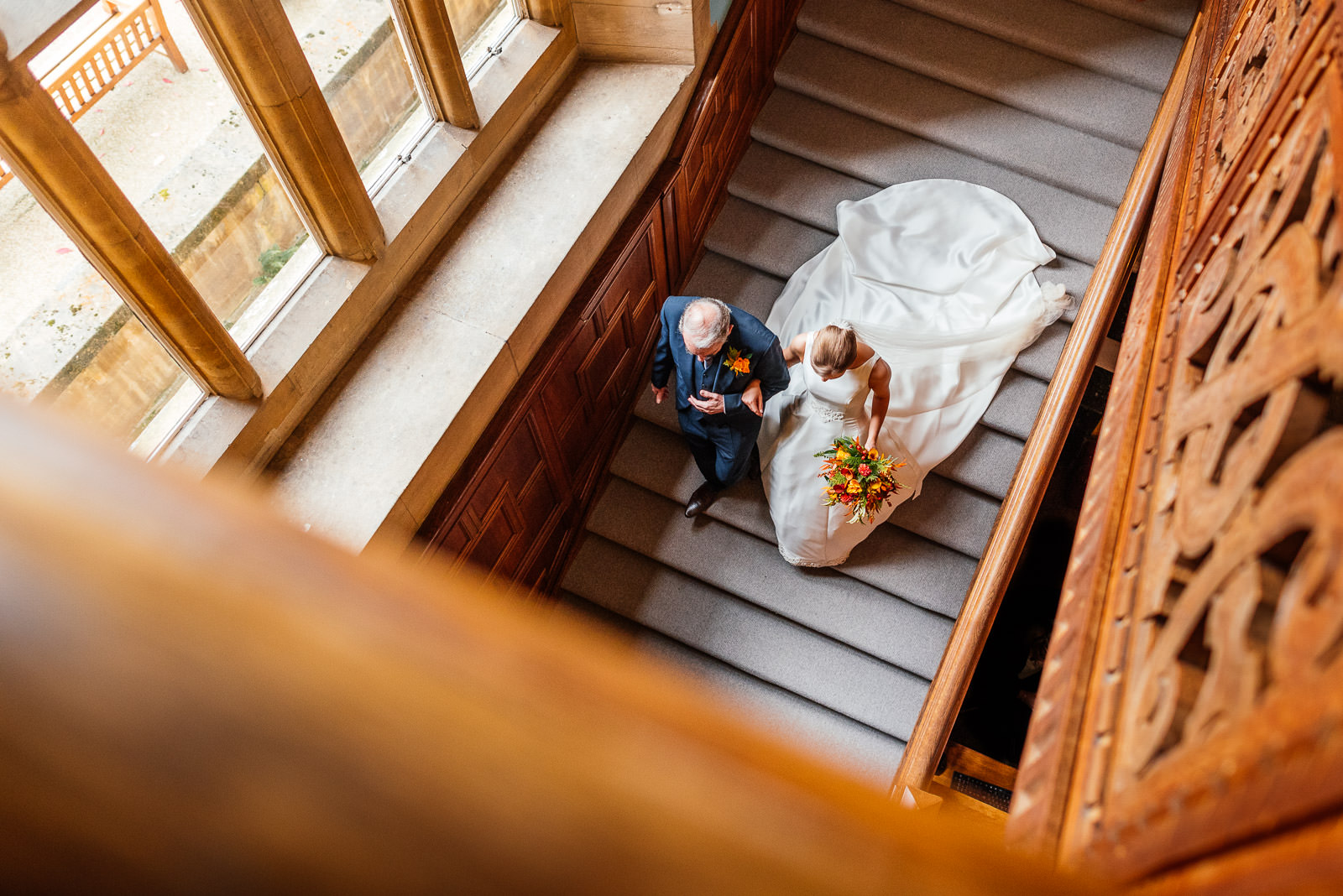bride walking with father down staircase