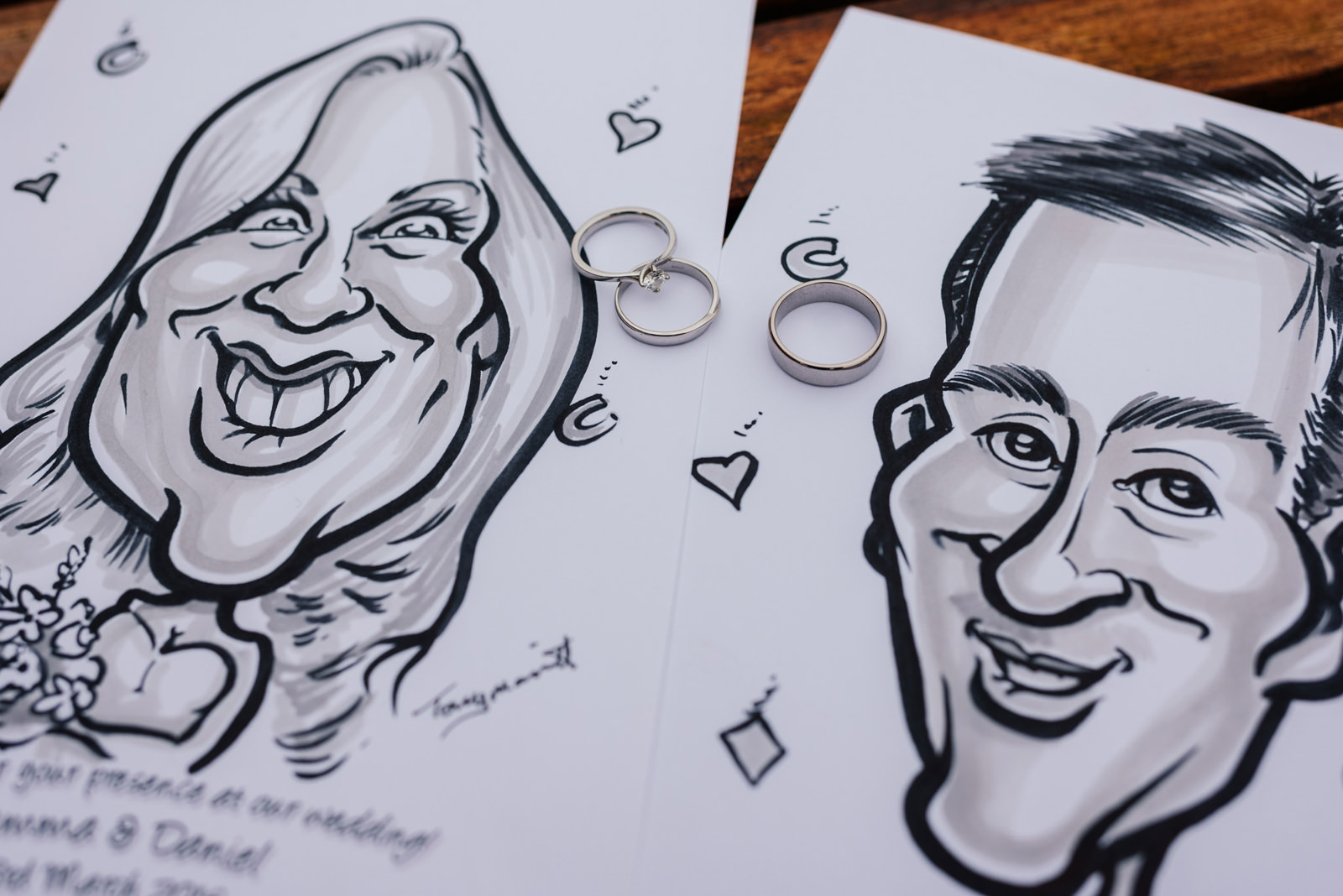caricature drawings of the bride and groom with their wedding rings