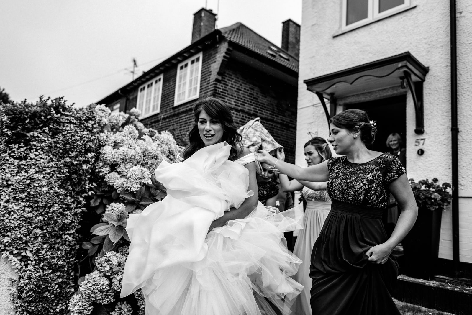 bridesmaids helping bride to the taxi in the rain