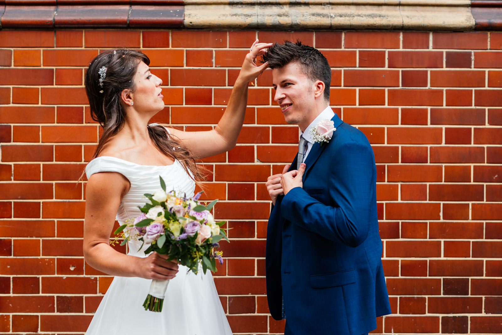 bride removing confetti from grooms hair