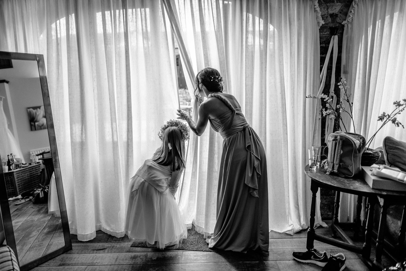 flower girl and bridesmaid looking out of the window