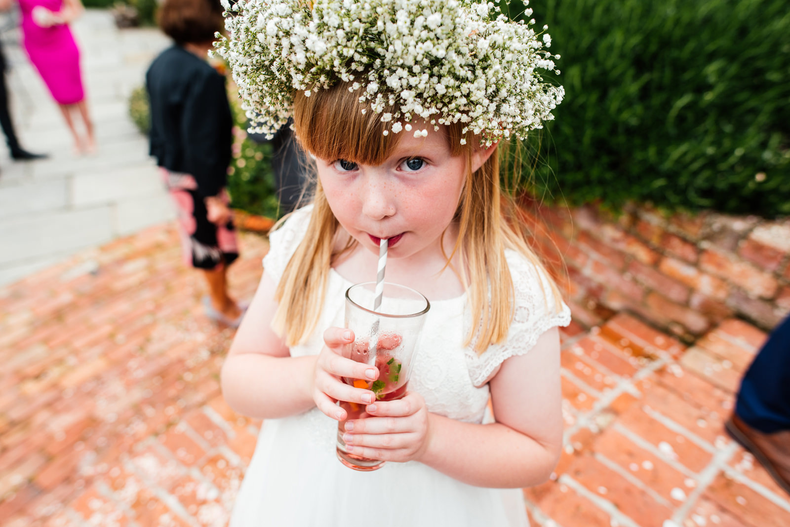 flower girl having a cheeky drink with straw