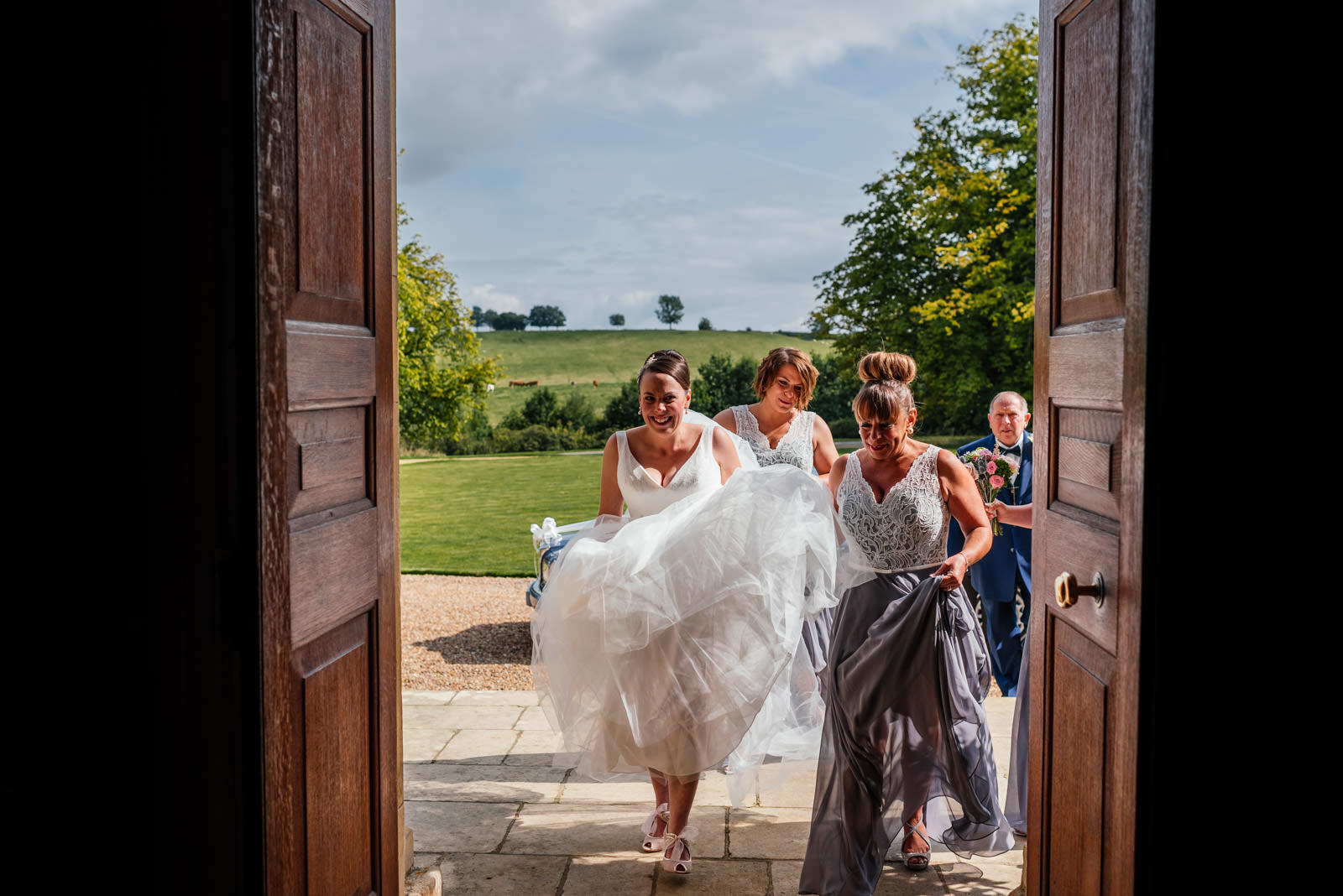 bride and bridesmaids walking in to the hall