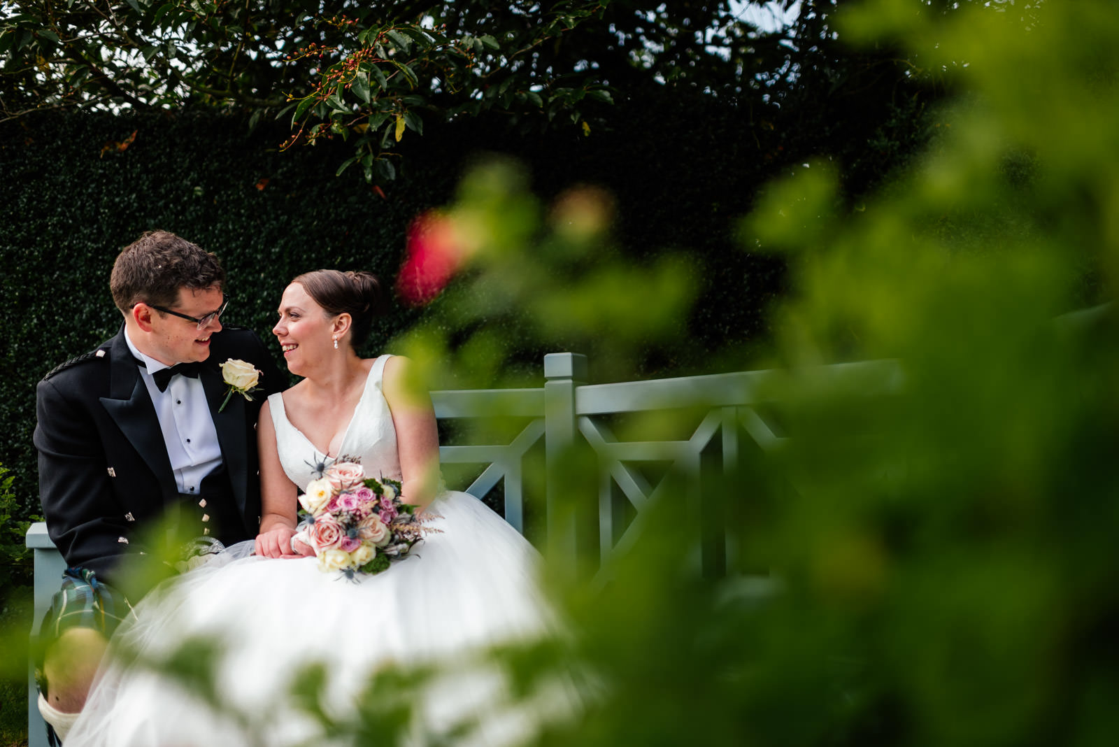 bride and groom portrait sitting down on bench in the garden