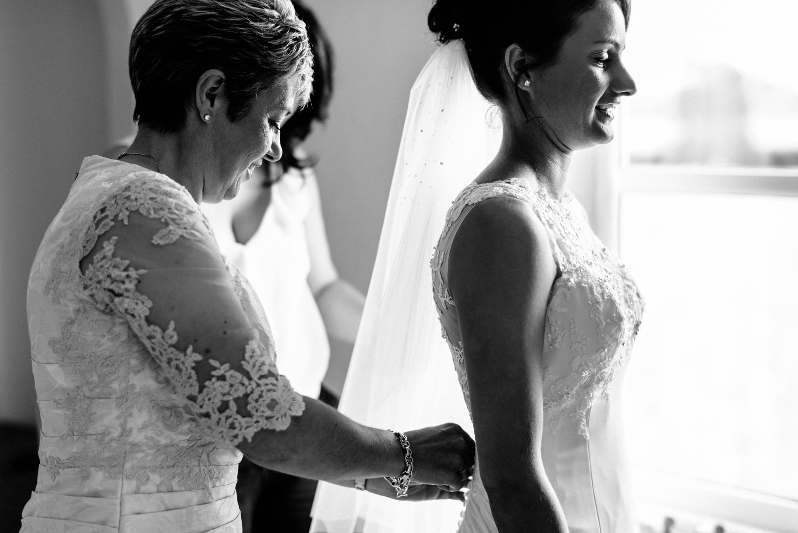 mother of the bride helping bride into her dress