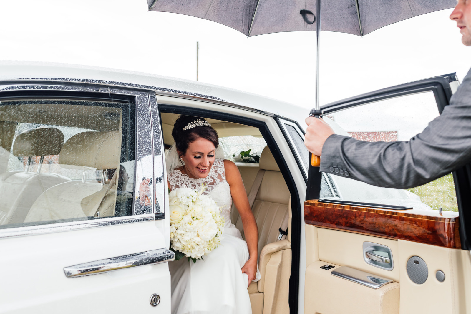 bride leaving the wedding car under umbrella