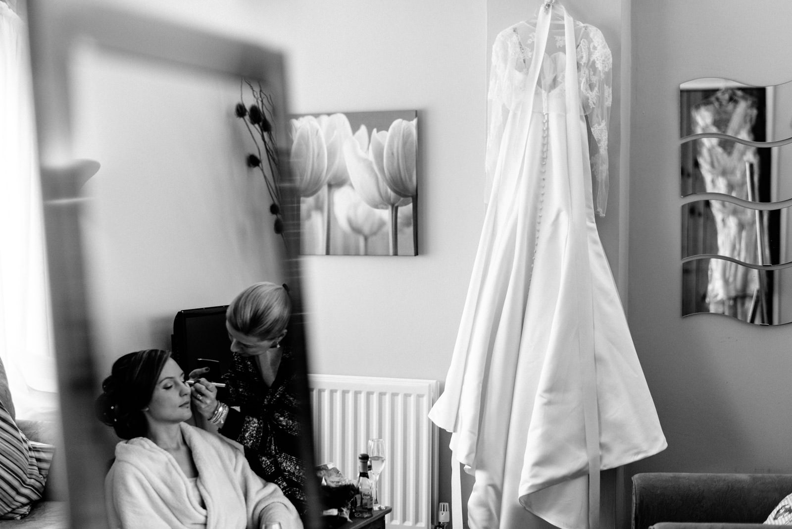 Photo of wedding dress and bride having make-up done