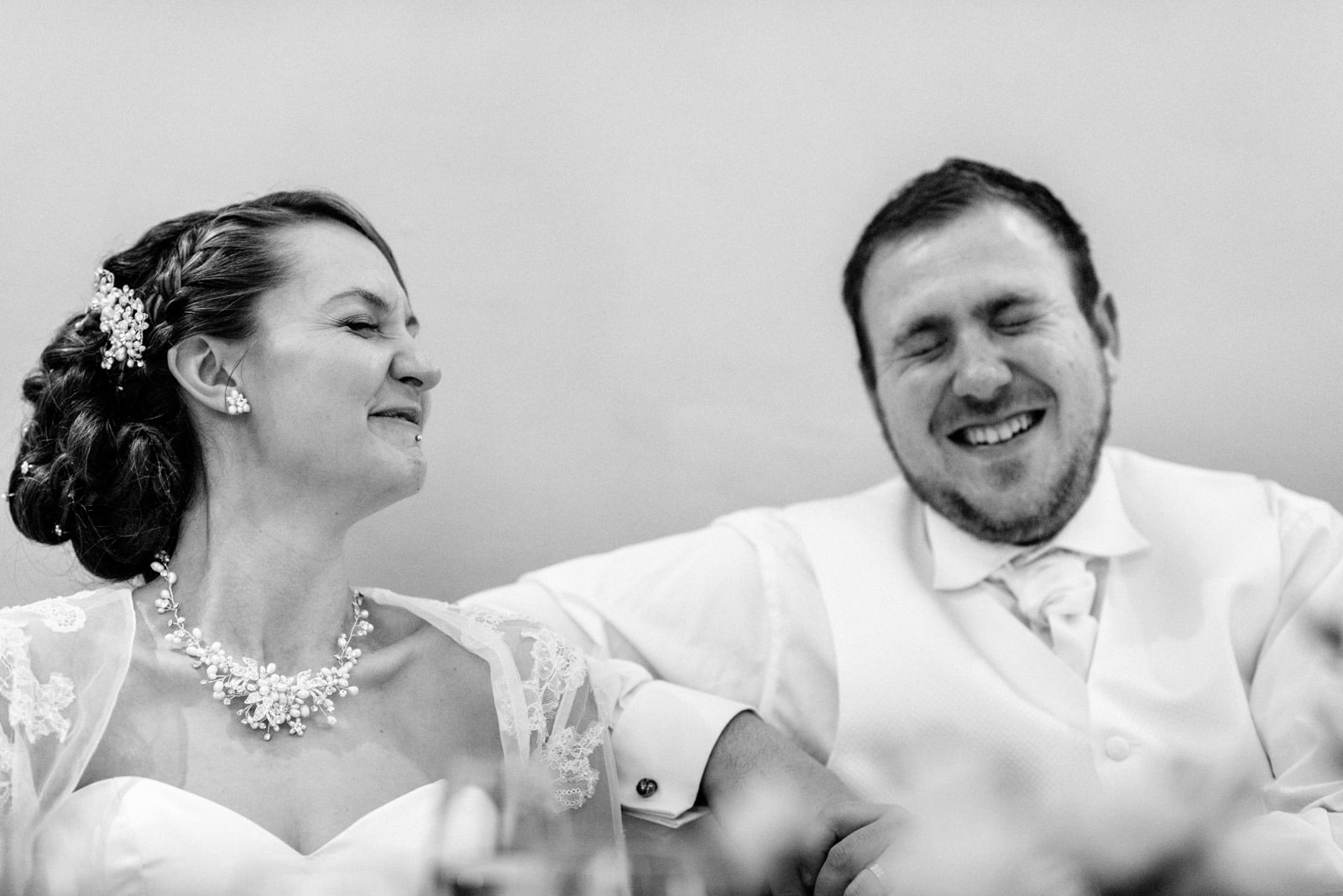 bride and groom laughing to speeches