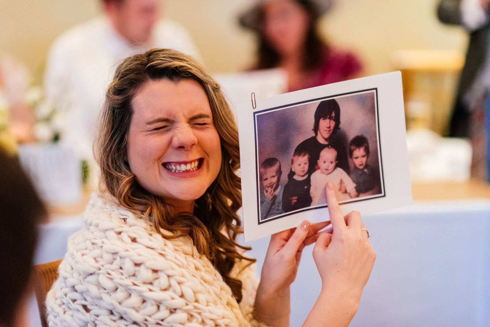 bridesmaid smiling whilst showing a photo of the groom as a child