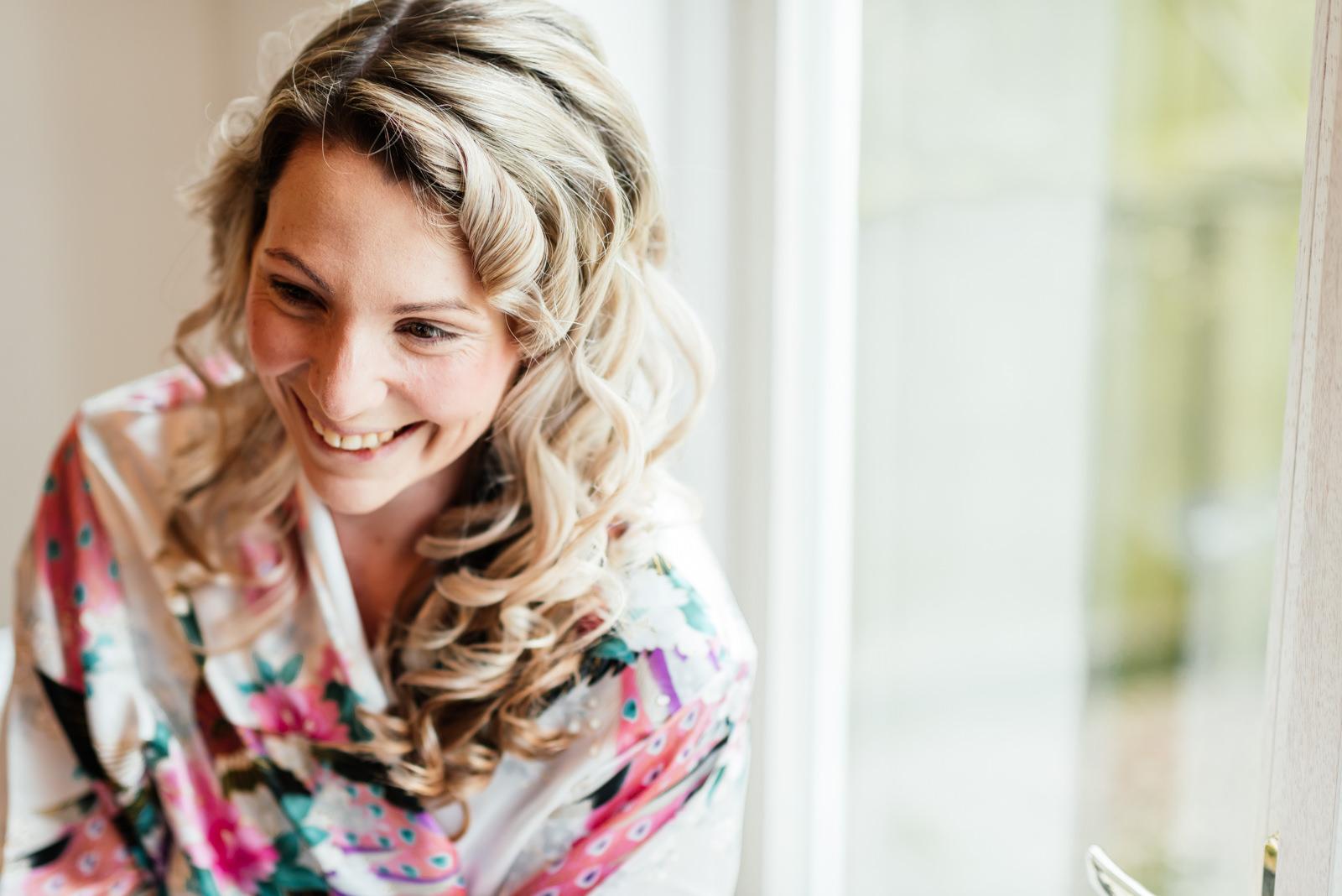 bride smiling during make-up for wedding