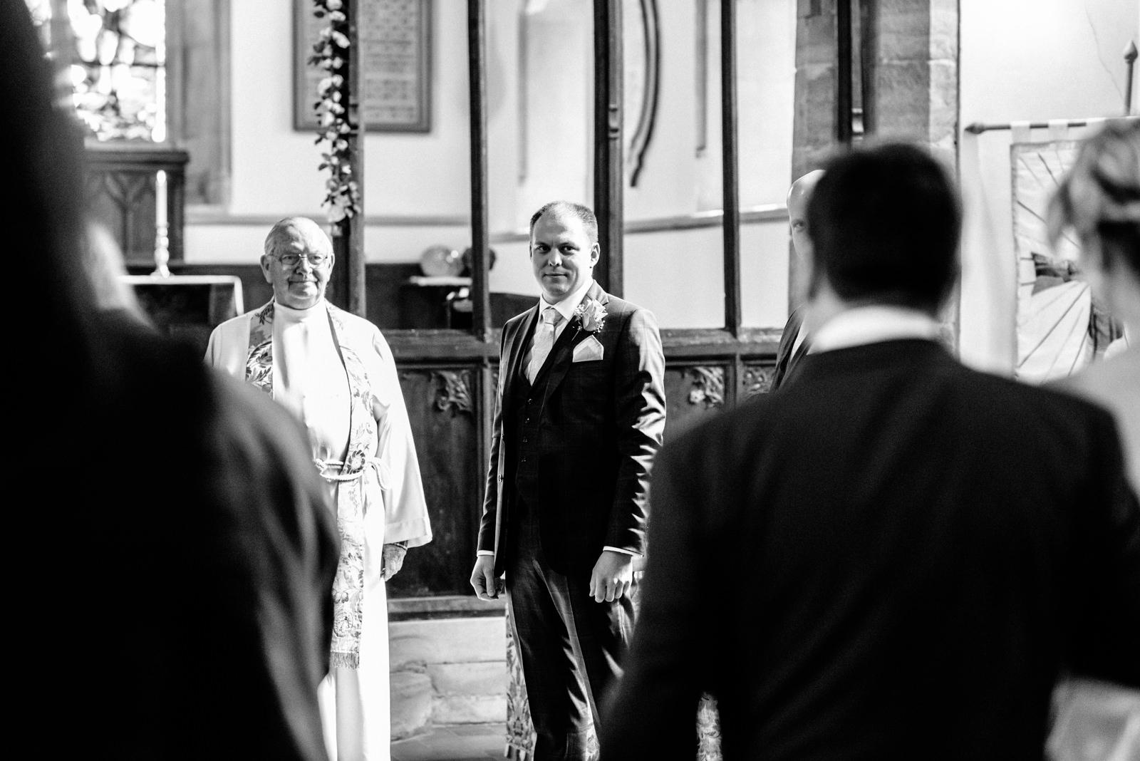 groom watching as bride walks down the aisle
