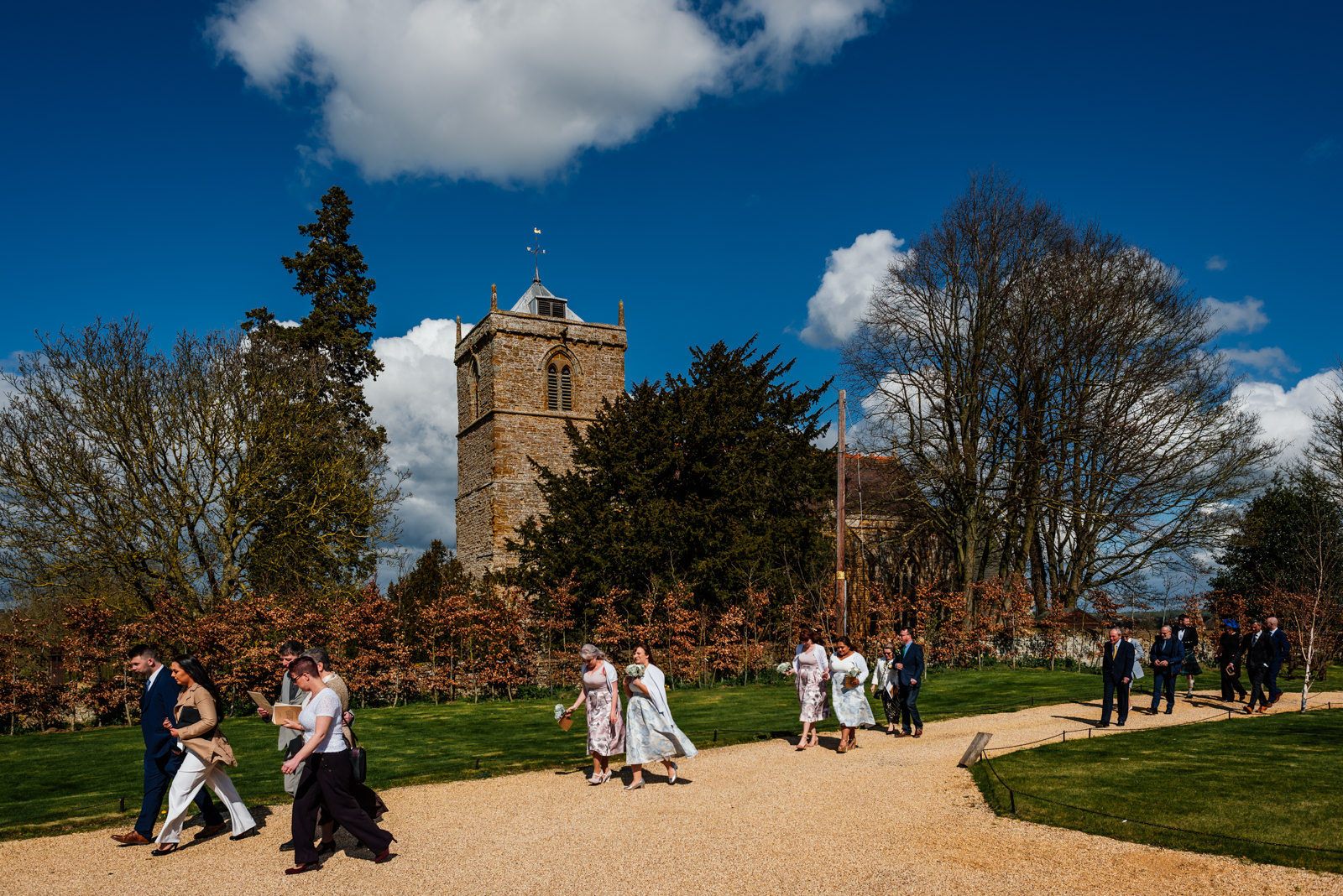 guests walking from church to Dodford Manor - blue sky