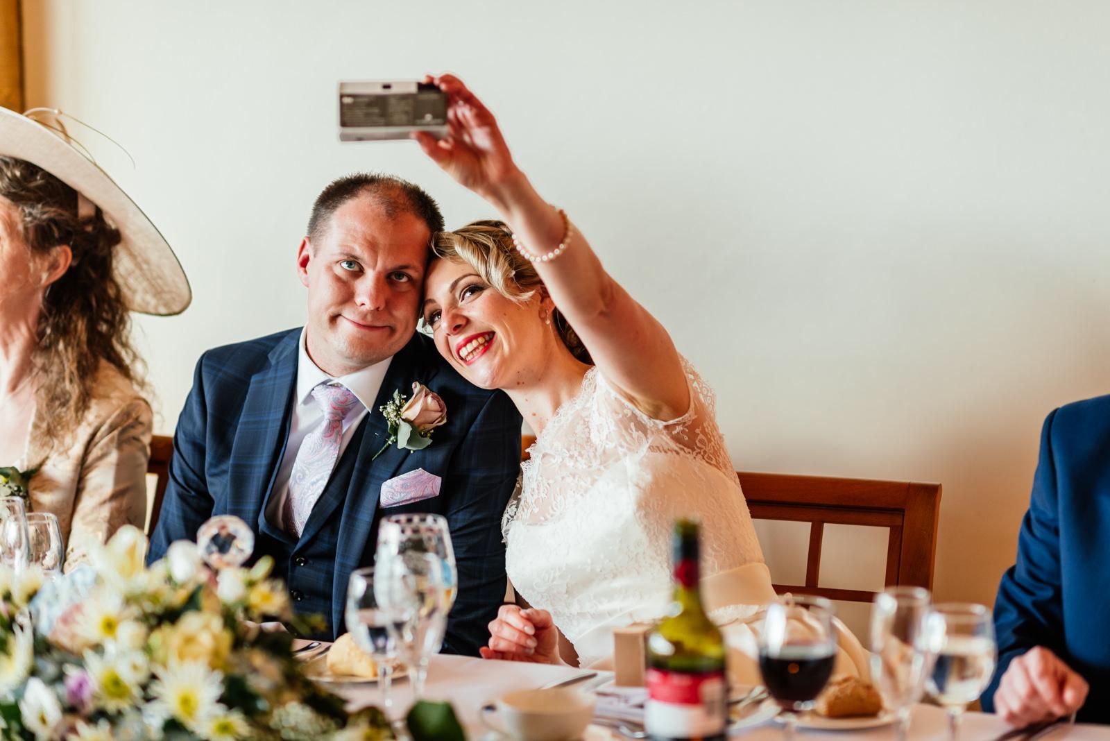 bride and groom take selfie