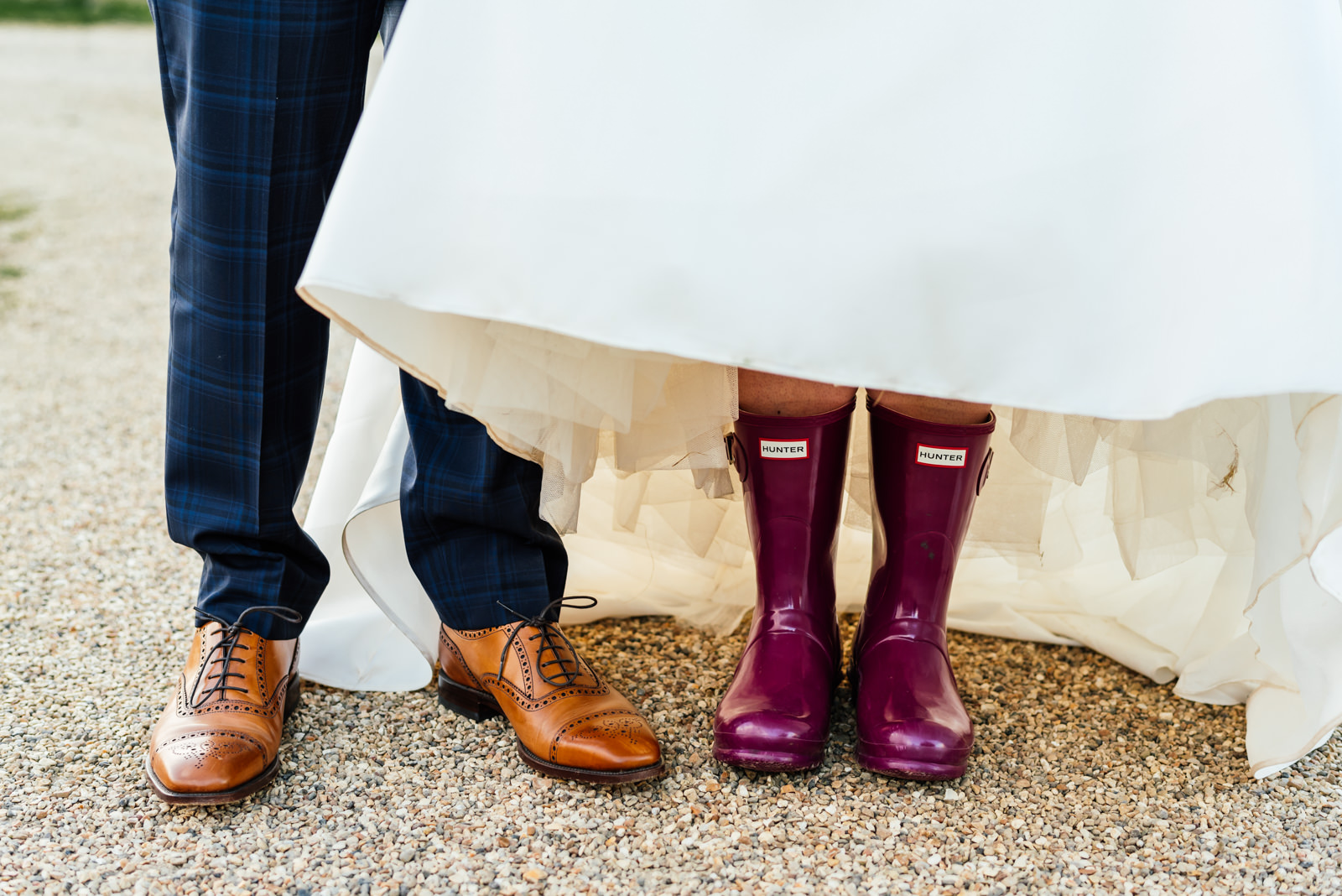 grooms shoes and bride wearing hunter welly boots