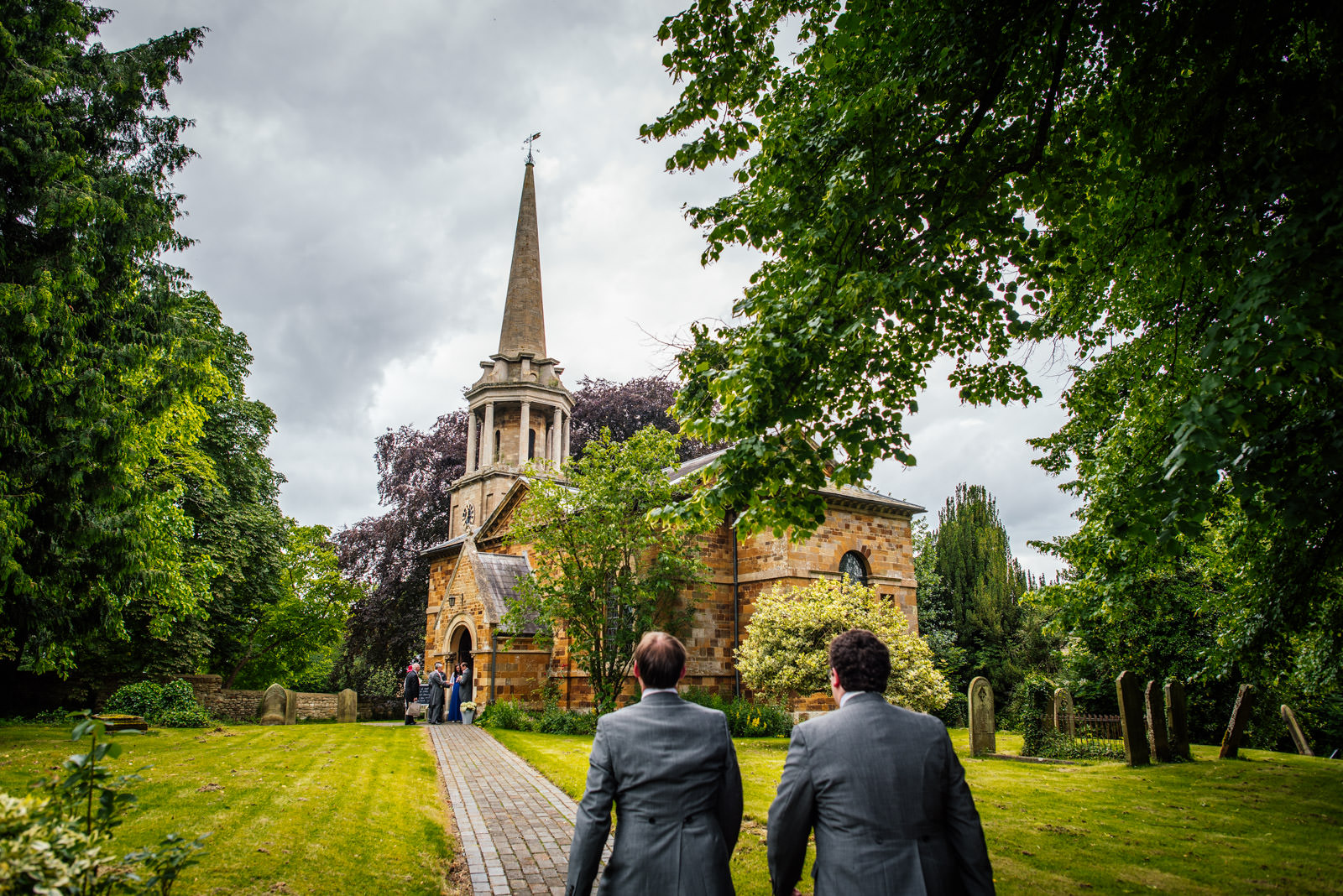 groom and groomsman walk to the church