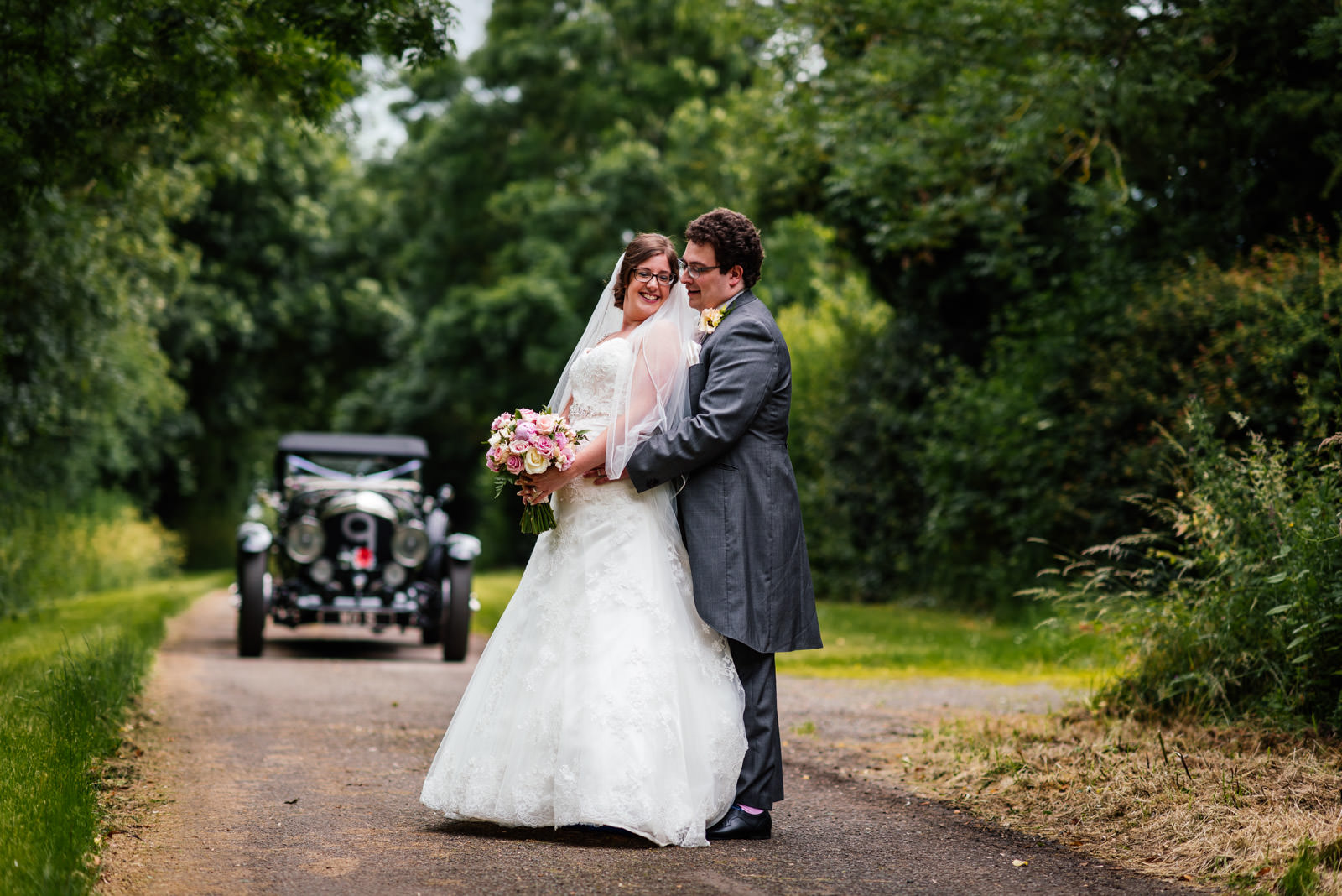 bride and groom portrait in front of vintage car