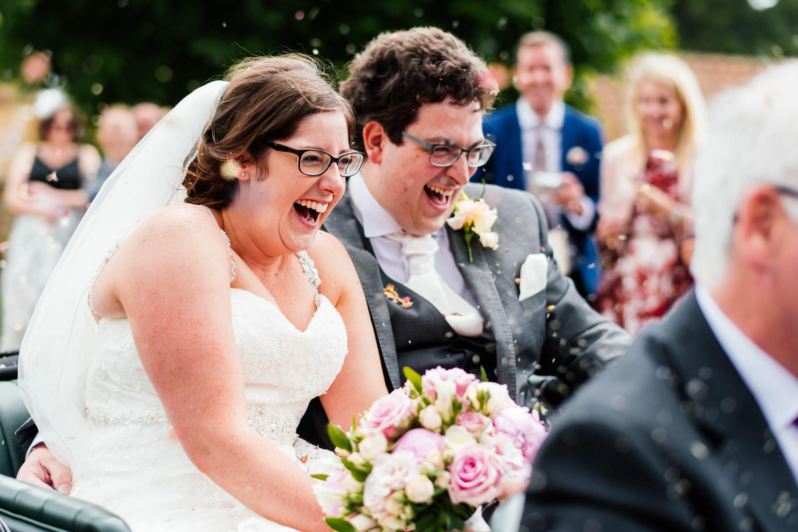 bride and groom arriving at reception venue with guests throwing confetti
