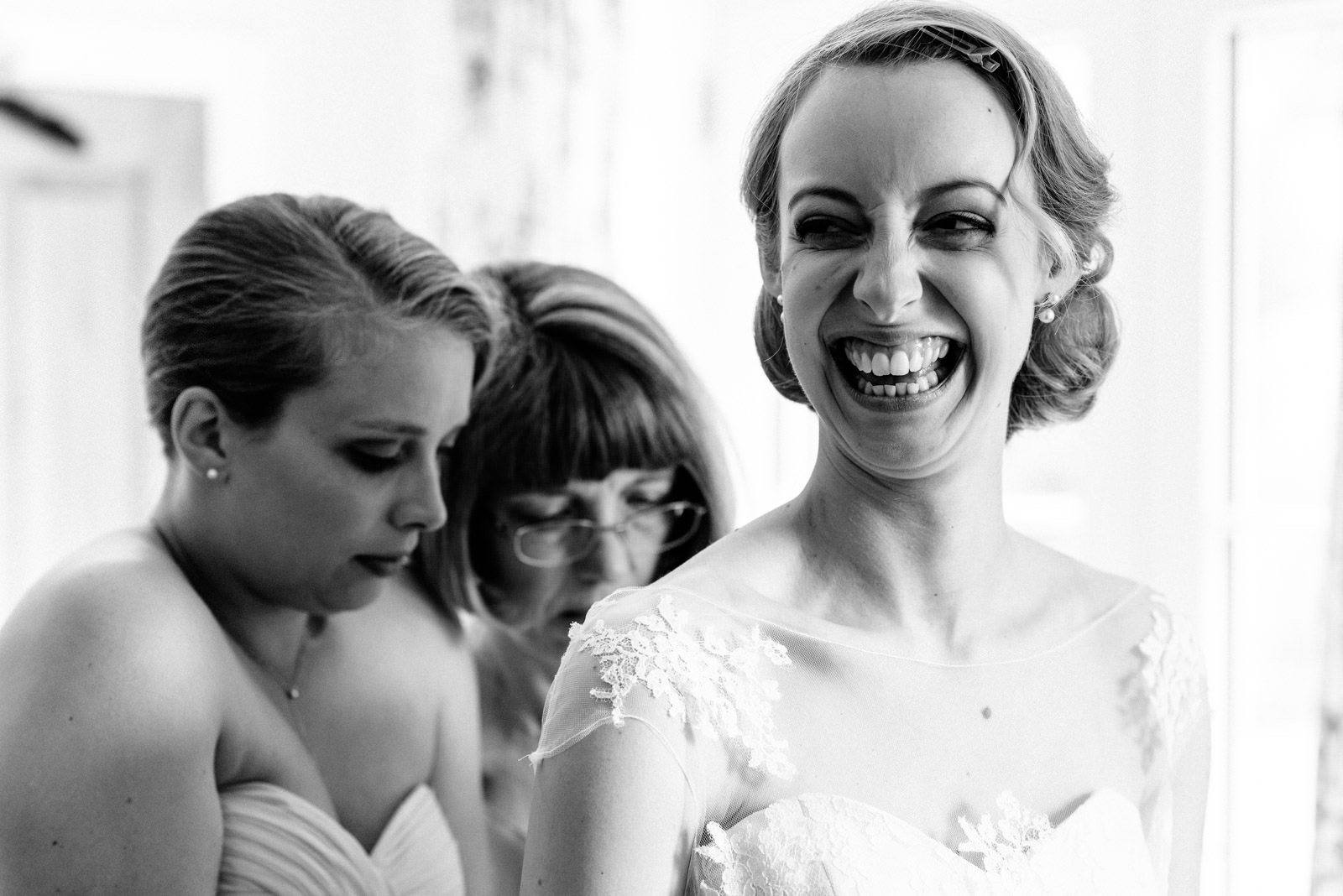 bride smiling while mum and bridesmaid help get her in dress
