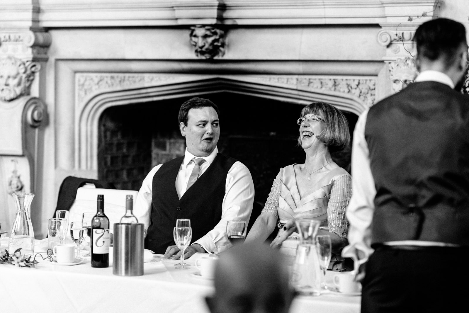 best man pulling funny face and mother of the bride laughing