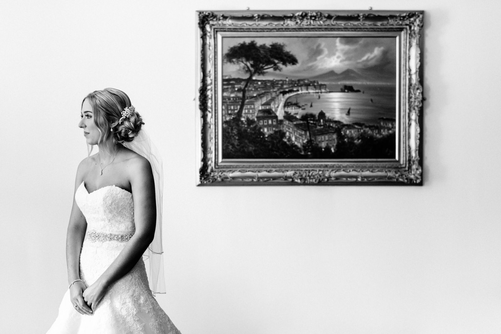 bride looking out of the window next to painting