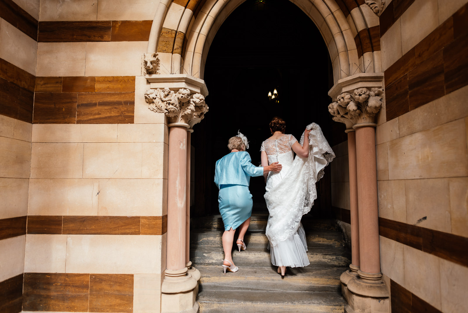 Mother of the bride helping the bride into the guildhall
