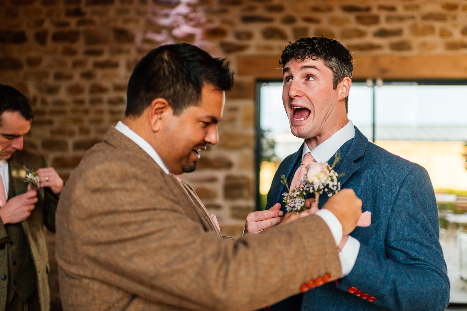 groom messing around when putting on his button hole