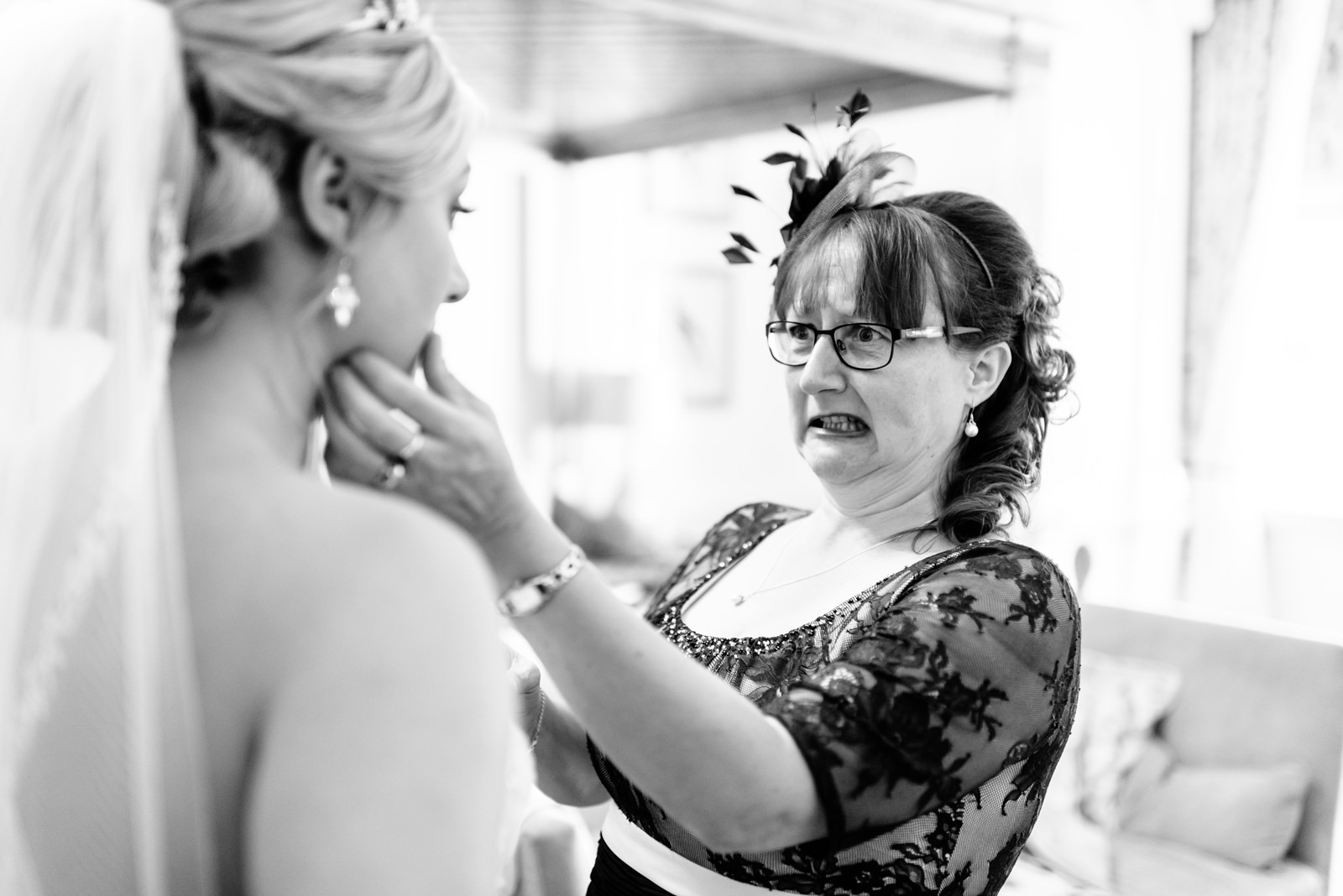 mother of bride adjusts bride's make-up