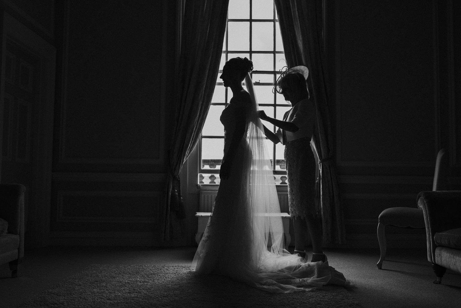 Mum helps bride into wedding dress