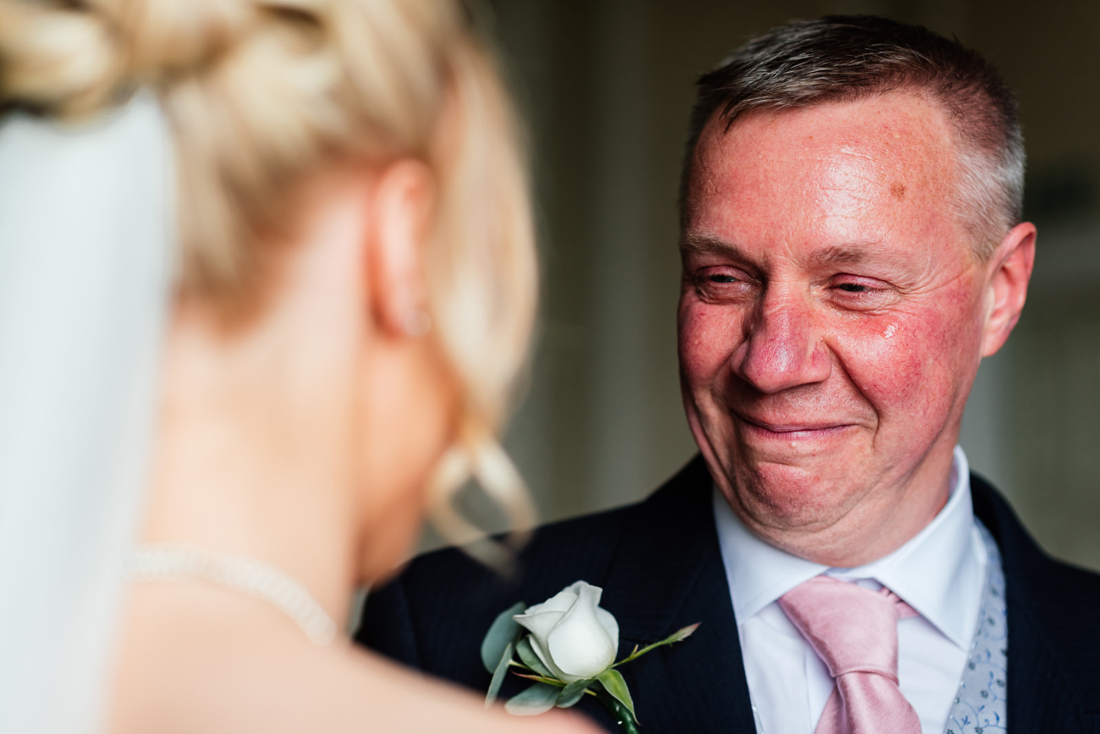 father with tear in his eye at seeing his daughter in wedding dress