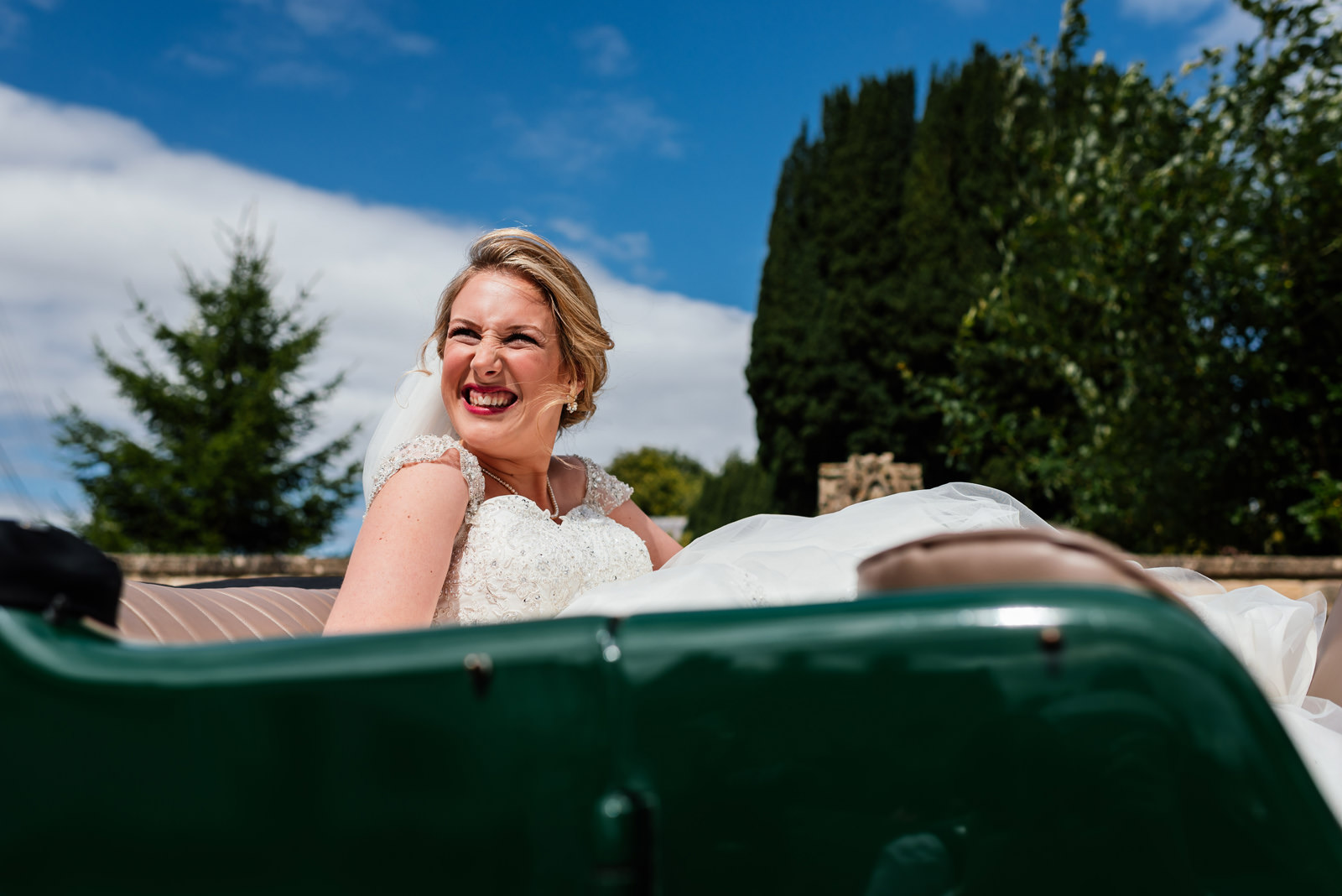 bride in the sunshine in vintage green car