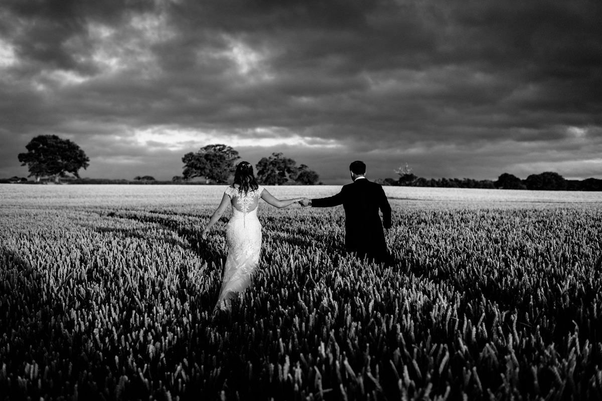 bride and groom walking out into corn field