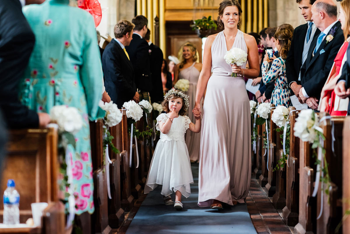 flower girl with flower crown walking down aisle