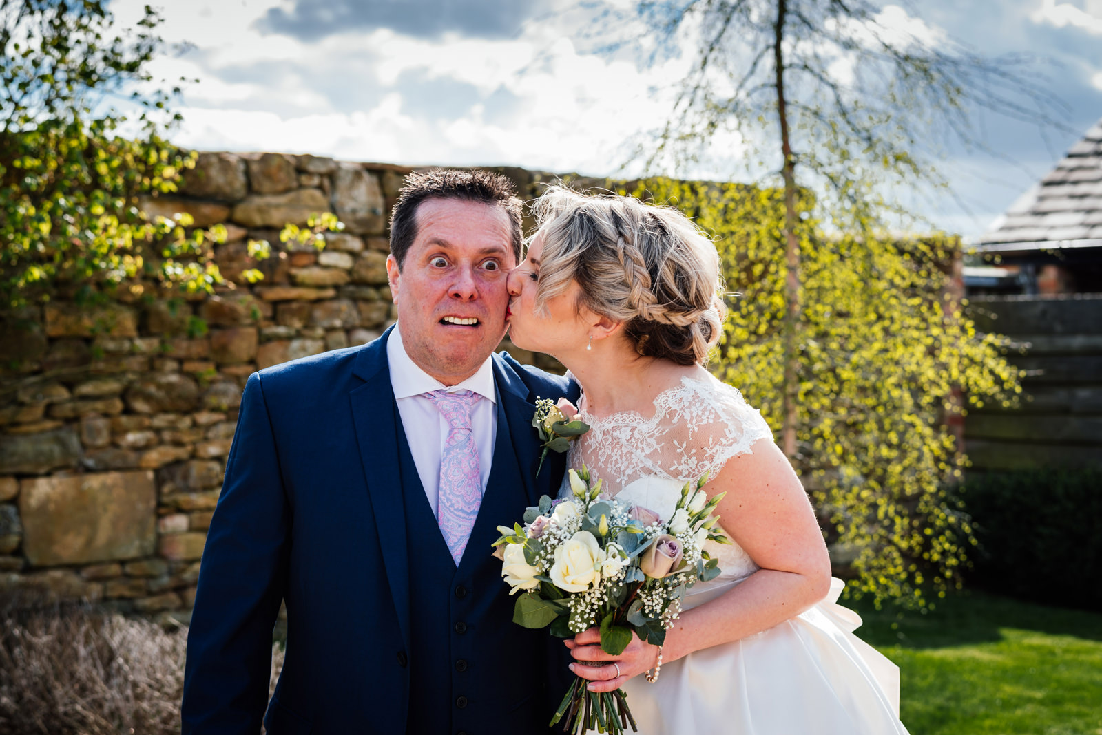 father of bride pulling funny face when being kissed by bride