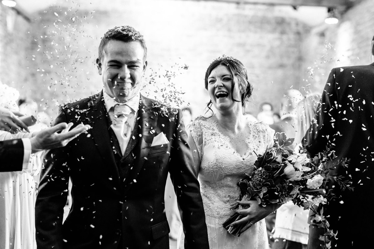 bride laughing during confetti walk through