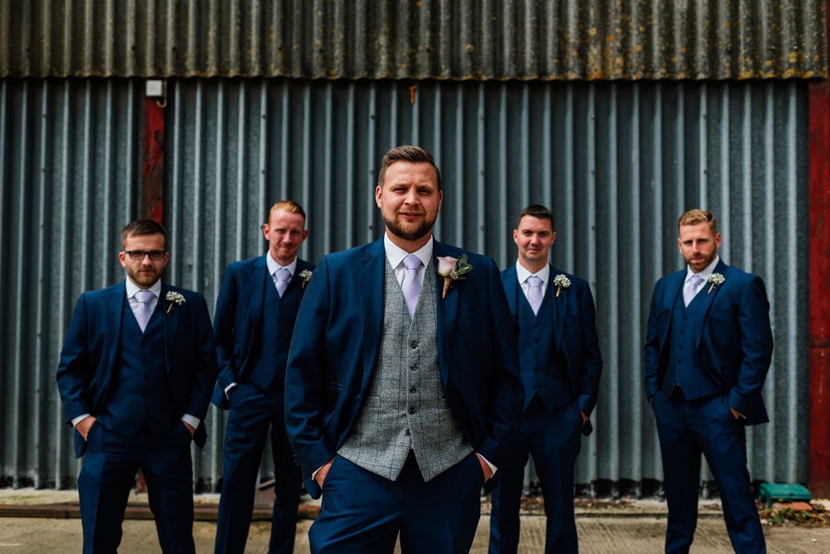 groomsmen group photo in front of farm barn
