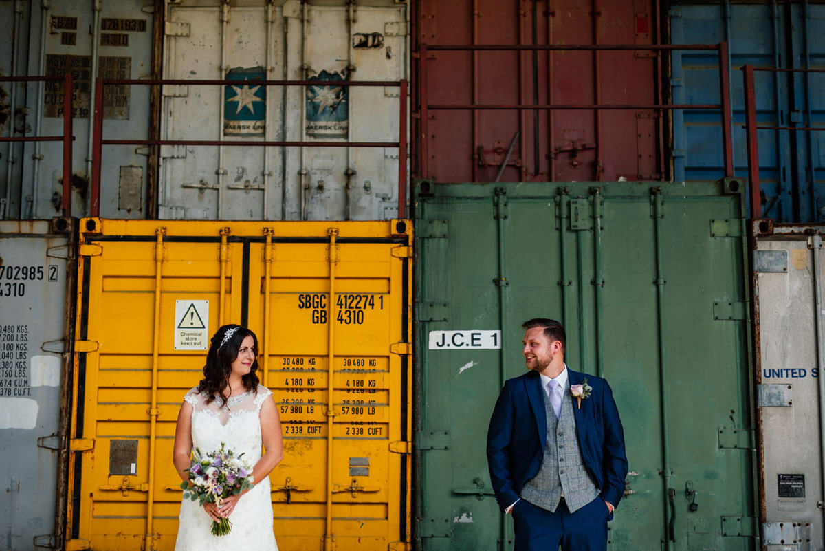 Bride and groom in front of the shipping containers at crockwell farm