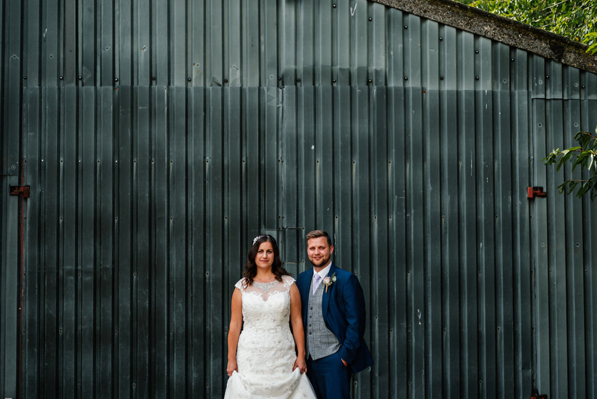 bride and groom in front of farm barn