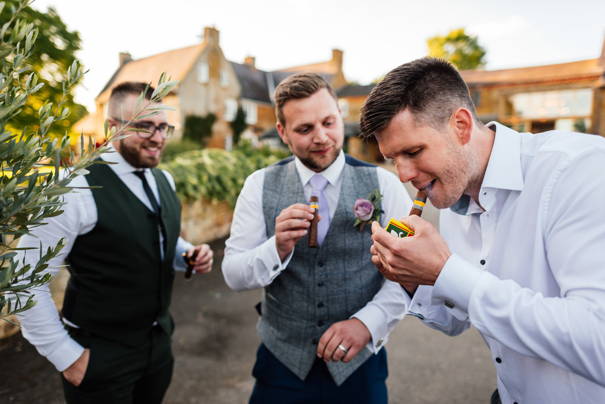 the groom and friends having a cigar