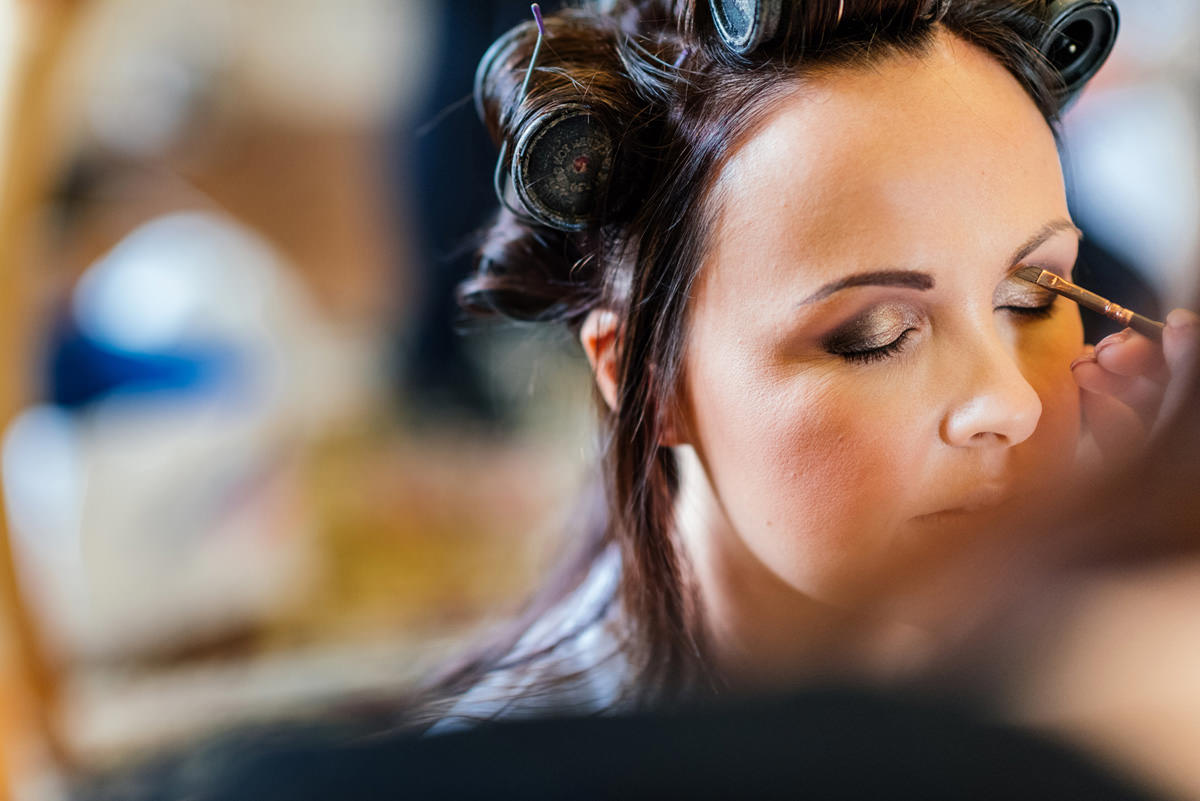 Bride having make up done on the morning of wedding day
