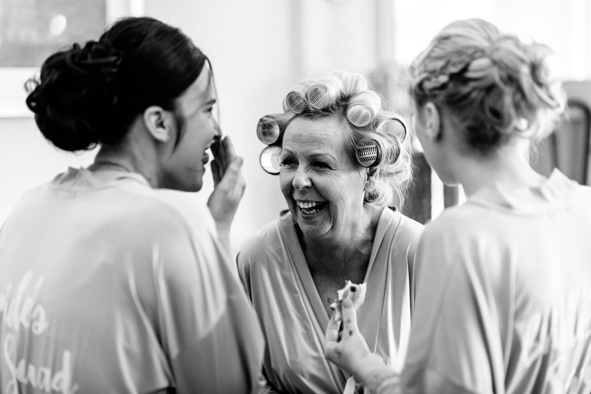 Bride's mum and bridesmaids laughing during morning prep